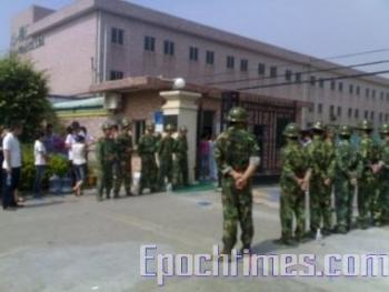 Police guard the gates at the factory. (The Epoch Times)