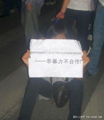 A female student holding a sign at the protest scene. (The Epoch Times)