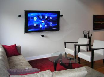 WIRED TO ENTERTAIN: A clean and wire-free home theatre in the Sohowest living room with a wall-mounted LCD TV. All the components are out of sight in the basement and connected to the TV through in-wall wiring. (Cindy Chan/The Epoch Times)