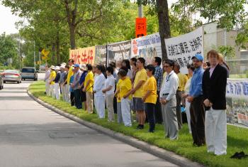 Falun Gong practitioners display banners in front of the Chinese embassy to raise awareness about the persecution of their practice by the Chinese regime that has persisted July 20, 1999. (Johansson Ren/The Epoch Times)