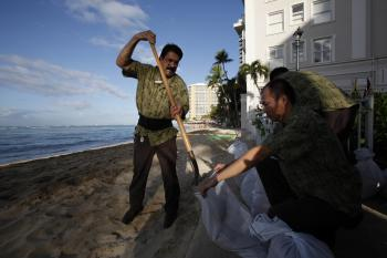 Workers make sandbags along Waikiki Beach behind the Westin Moana Surfrider hotel on Feb. 27, 2010, in Honolulu, Hawaii. Residents are stocking up on food and emergency supplies in preparation for a potentially damaging tsunami, after a massive 8.8-magnitude earthquake hit central Chile sending waves across the Pacific Ocean. Hawaii is under a tsunami warning. (Kent Nishimura/Getty Images)