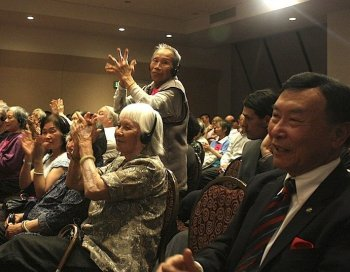 An elderly man wearing a pro-Central Subway sticker stands and claps enthusiastically during the Wednesday San Francisco mayoral candidates' debate at the Chinese Cultural Center. He was amidst a large group of elderly Chinese with similar pink stickers sitting front and centre near the stage. (Matthew Robertson/The Epoch Times)