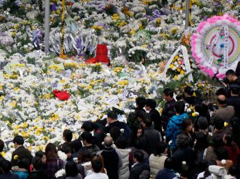 Shanghai's Jiaozhou Road turns into a sea of flowers on Nov. 21 as tens of thousands of people mourn where 58 people were killed in a high-rise apartment fire a week ago. (Epoch Times Archives)