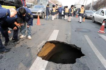 Chinese workers inspect a sinkhole in a street in Beijing on Feb. 8. Sinkholes are known geological phenomena that usually occur predominantly in areas that have been heavily mined or on reclaimed land. (AFP/Getty Images )