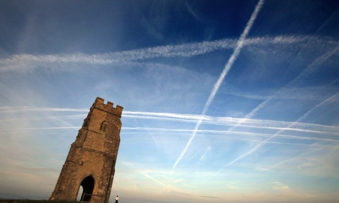 A woman looks up at the mass of contrails left by a jet aircraft crossing the sky above St. Michael's Tower near Glastonbury, England. (Matt Cardy/Getty Images)