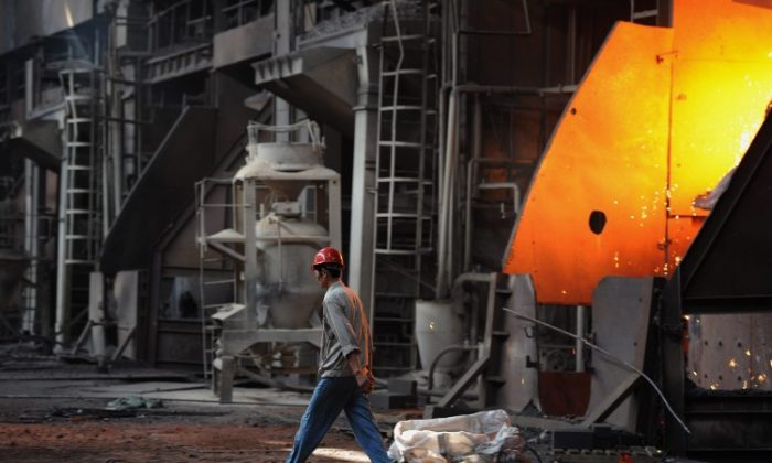 A worker walking past a giant cauldron at a steel mill in Anhui province on June 25, 2011. (STR/AFP/Getty Images)