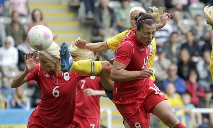 Canada's Melissa Tancredi heads home her country's second goal against Sweden on Tuesday. (Graham Stuart/AFP/Getty Images)