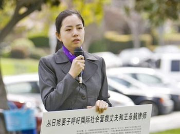 Tian Lu speaks at a rally celebrating 90 million quitting the Chinese Communist Party at Barnes Park in Monterey Park, California, on March 6. In her hand, Ms. Tian holds a placard describing the cases of her husband, Cong Rixu, and his lawyer. (Ji Yuan/Epoch Times)