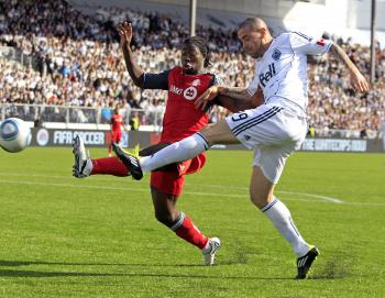 Eric Hassli (R) of Vancouver Whitecaps FC and Nana Attakora of Toronto FC contest for the ball in a highly entertaining game last Saturday. (Jeff Vinnick/Getty Images)