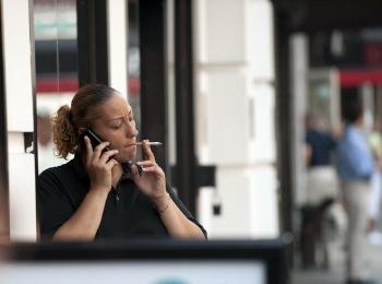 A woman smokes a cigarette outside an office building. All territories and provinces as well as the federal government in Canada ban smoking in indoor public spaces and workplaces, including restaurants, bars, and casinos. (Don Emmert/AFP/Getty Images)