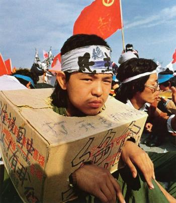 May 15th: A Beijing university student sits bound in a cardboard box as the strike for democracy continues for the third day in Beijing's Tiananmen Square. The box indicates he cannot use his hands, serving as proof that he cannot eat. (64memo.com)