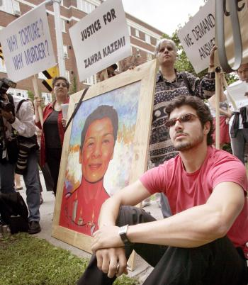Stephan Hashemi sits with a portrait of his mother, Zahra Kazemi, at a protest outside the Iranian embassy on July 16, 2004 in Ottawa. Ms. Kazemi, a Canadian photojournalist of Iranian descent, died from torture a year earlier after she was arrested for taking pictures of demonstrators outside Tehran's Evin prison. (Patrick Doyle/Getty Images)