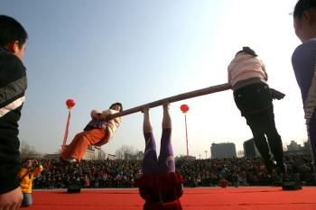 Balancing a bar to support two women. (AFP/Getty Images)