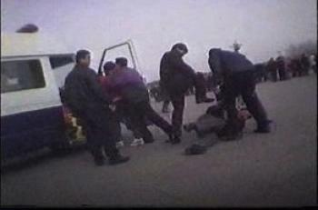Plain-clothes police kick a Falun Gong practitioner in Tiananmen Square, Beijing as another is forced into a waiting police van in a clip from the upcoming CBC documentary Beyond the Red Wall: The Persecution of Falun Gong.  (CBC)