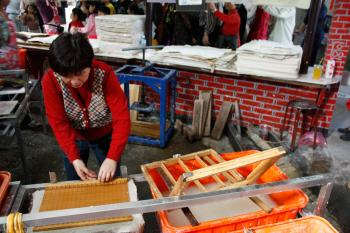 Wu Shuli giving a demonstration of the paper making process in the miniature troughs for school students; a school groups moves past in the background. (Matthew Robertson/The Epoch Times)