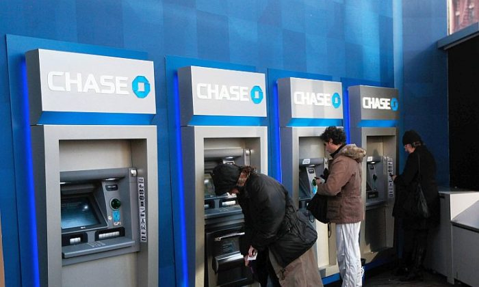 People use ATMs at a Chase branch bank in New York City. Banks are important for the economy but their lending practices lead to inequality. (Chris Hondros/Getty Images)