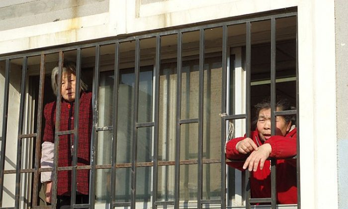 Petitioners Ms. Chen Bixiang (left) and Ms. Yu Hong (right) during their detention at a Beijing black jail in Jan. 2012. Ms. Chen, in her seventies, was beaten by guards. (Courtesy of a source in China).