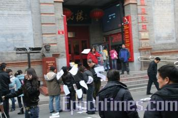 Chen Mingguang from Hubei Province disseminating a thousand fliers in Beijing's oldest and most famous busy business district, Dec. 8. (The Epoch Times)