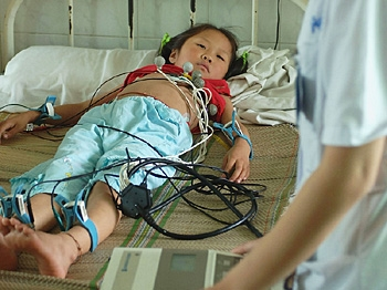 A nurse checks the cardiogram of a young girl sickened during a vaccine accident at a hospital in China.   (China Photos/Getty Images)