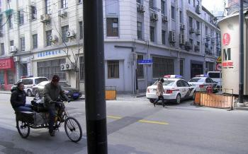 Police vehicles lined up outside Duan's home the day of the memorial service. (The Epoch Times)