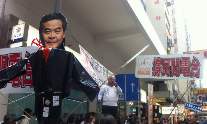 """A group of city residents hold up a banner that says """"New Year's March"""" with a picture of Leung Chun-ying being thrown into the trash bin by a large hand. The procession is about to stomp on the image on the ground, consisting of a crossed-out """"Communist"""" character outlined in red."""