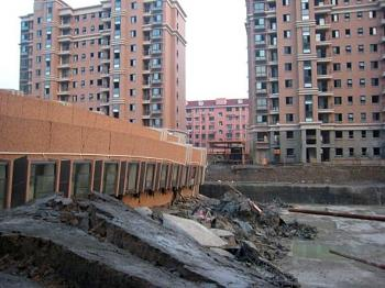 The building simply toppled over, leaving a gap between the surrounding, identical structures. (Internet photo)