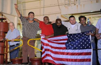 FREEDOM REIGNS: Crew members of the US merchant ship Maersk Alabama gather around a US flag while celebrating that the captain of their ship which had been held captive by the pirates had been freed on Sunday.  (Roberto Schmidt/AFP/Getty Images)