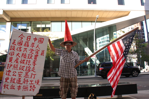 Michael Hull wears a homemade hat during a protest outside Alice Tully Hall, Lincoln Center, Sept. 15. (Cai Rong/The Epoch Times)