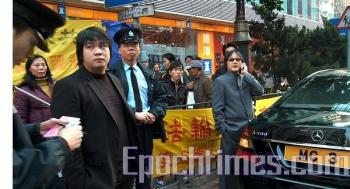 Police question two suspects (man on right in gray suit and man on left in black suit) in the attack against the booth organized by practitioners of Falun Gong.  (The Epoch Times)
