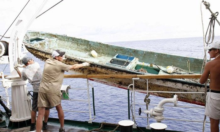 Crew from the Russian ship STS Pallada prepare to hoist a Japanese fishing boat on board. The Pallada came upon the boat floating among debris from the Japanese tsunami on its homeward voyage from Honolulu to Vladivostok in September. (Courtesy of Pallada)