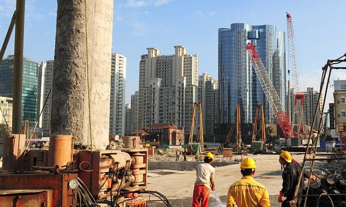 Laborers work at a new property development under construction on the busy Nanjing Road shopping street in Shanghai, Oct. 9, 2011. China has invested heavily in property--about $750 billion in 2010 alone--since it privatised the market in the late 1990s, ending decades of state allocated housing and enabling a growing middle class to own their own homes. A massive stimulus package unveiled in late 2008 to combat the global financial crisis also funnelled a large portion into construction. (Mark Ralston/AFP/Getty Images)