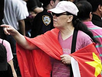 Li Huahong wrapped in a Chinese regime flag on May 31, 2008, in Flushing. Li is known for spreading propaganda to Chinese people in Flushing. (The Epoch Times)