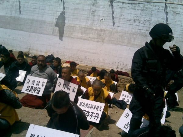 Tibetan monks on their knees, hands tied behind their backs