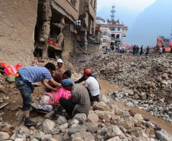 Surviving residents cover the body of a deceased relative resting on a makeshift stretcher amid the rubble of landslide devastation as rescue efforts continue in Zhouqu on August 11, in northwest China's Gansu province. (Frederic J. Brown/Getty Images )