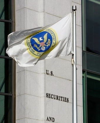 A flag flies in front of the U.S. Securities and Exchange Commission building in Washington, DC. Peter Siris, a stock promoter, has recently been charged with securities law violations by the SEC.  (Chip Somodevilla/Getty Images)