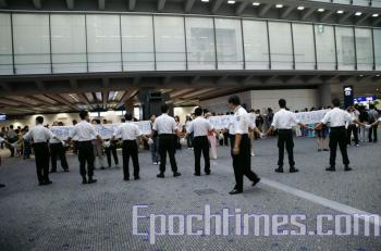 Hong Kong police form a human shield to stop Falun Gong practitioners from entering Hong Kong. (The Epoch Times)