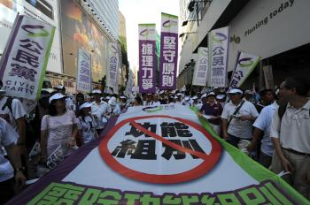 Pro-democracy protestors carry a banner reading 'no to the functional constituency' as they attend a pro-democracy rally in Hong Kong on July 1, to protest Hong Kong's Legislative Council electoral reform that promises to fundamentally change Hong Kong's relations to Beijing. (Daniel Sorabji/Getty Images)