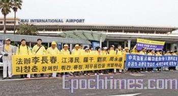 Li Changchu, member of Chinese Communist Party Politburo Standing Committee, visited South Korea on April 4. Falun Gong practitioners in South Korea gathered at the Cheju Airport with banners. (The Epoch Times)