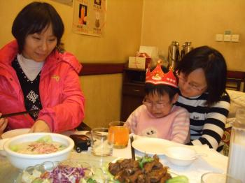 SAD BIRTHDAY: Qingqing on her sixth birthday in November 2009. She cries at the dinner table with relatives because her mother and father were in labor camps.  (Courtesy of Minghui.net)