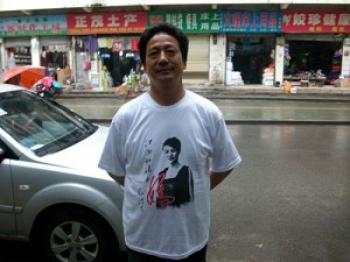 A man wearing a T-shirt with words in support of Deng Yujiao. (The Epoch Times)