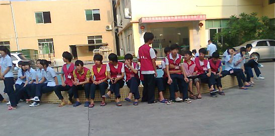 Child workers sit outside their factory
