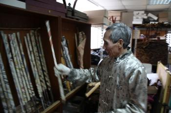 Chen laughs as he puts back one of his incomplete swords into the rack, on the left. Wrapped in newspaper in his attic, each is worth thousands. (Matthew Robertson/The Epoch Times)