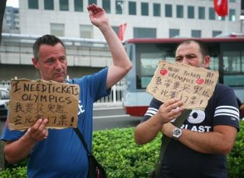 This picture was posted on the internet shows Olympic visitors wandering the streets of Beijing with signs advertising their wish to buy tickets. (Screenshots from internet)