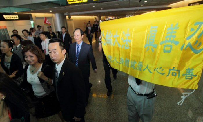 "Guangdong governor Huang Huahua on a state visit to Taiwan is met by Falun Gong practitioners holding up banners saying, ""Falun Dafa -Truth-Compassion-Forbearance"" at Taoyuan Airport, Aug. 16, 2010 (minghui.org)"