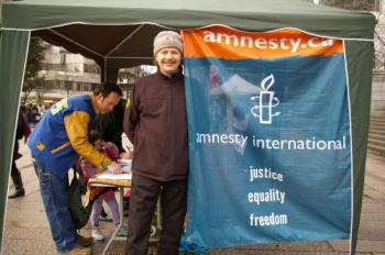 A man signs a petition at an Amnesty International booth in Vancouver during a Human Rights Day rally on Wednesday. (Sherry Dong/The Epoch Times)