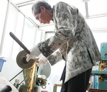 Chen demonstrates how he grinds the steel bars into swords in his workshop. It is a long and arduous process. The slightest of errors can ruin the blade, which would otherwise fetch thousands of dollars. (Matthew Robertson/The Epoch Times)