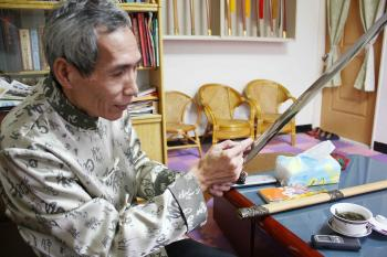 Chen Shih-Tsung, over 60 years old, explains the chemical reactions crucial to successful swordmaking. (Matthew Robertson/The Epoch Times)