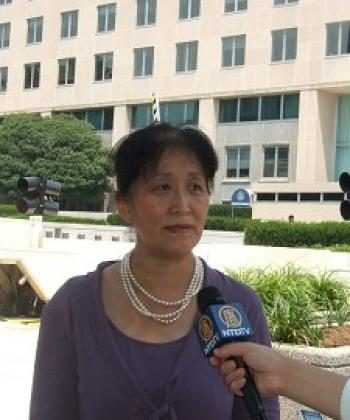 Falun Gong practitioner Wenyi Wang stands in front of the U.S. State Department headquarters. (Epoch Times)
