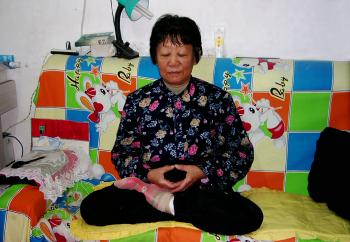 Chen Jun practices Falun Gong's sitting meditation at their home in Shenyang, Liaoning.  (Courtesy of Jing Tian)