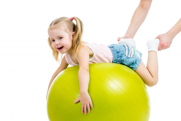 mother doing gymnastics with kid on fitness ball